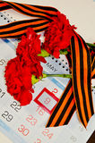 Three red carnations wrapped with George ribbon on the calendar with 9th May date - Victory Day still life Stock Images