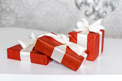 Three red celebration gift boxes with ribbon bows on white table. Stack of presents in luxury interior. Royalty Free Stock Photography