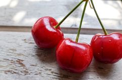 Three red cherries on wooden table n a sunny day. Three red cherries on wooden table in a sunnny day royalty free stock images