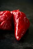Three red chili peppers on dark tray Stock Photo