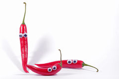 Three red chillis with googly eyes Royalty Free Stock Photo