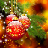 Three Red Christmas Balls hanging in front of Abstract Fir Tree Stock Image