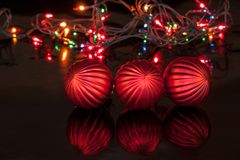 Three red christmas balls are lying on a mirror flooring. Christmas holidays Royalty Free Stock Photo