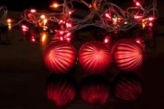 Three red christmas balls are lying on a mirror flooring. Christmas holidays Stock Photo