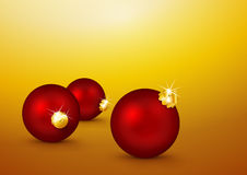 Three Red Christmas Balls lying on the Yellow Gold Background. Stock Photo