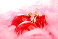 Three red christmas balls on pink fluff Royalty Free Stock Photography