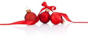 Three Red Christmas balls with ribbon bow Isolated on white Royalty Free Stock Photos