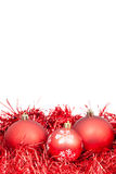 Three red Christmas balls and tinsel isolated Stock Photos