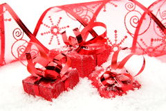 Three red christmas gifts with ribbon on snow Royalty Free Stock Photography
