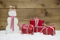 Three red Christmas presents and snowman with snow. Checkered red gift boxes for christmas with a snowman on a wooden background Royalty Free Stock Photography