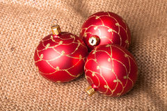Three red Christmas tree ball on sacking Stock Photo