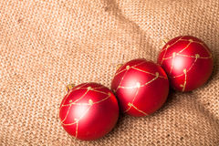 Three red Christmas tree ball on sacking Stock Photography