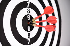 Three red darts in the target center Stock Photography