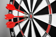 Three red darts in the target center Royalty Free Stock Photo