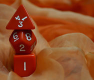 Three red dice and an orange scarf Royalty Free Stock Photo