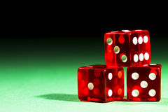 Three red dices. On green table and black background royalty free stock photo