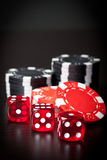 Three red dices and black and red chips Royalty Free Stock Images