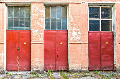 Three red doors bearing a danger label stock photo