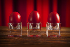 Three red eggs on wooden table Stock Photography