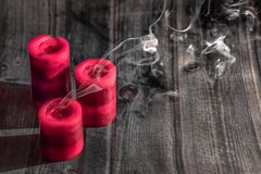 Smoke from three red candles, extinguished candles. Three red extinguished candles on wooden rustic table, beaytiful grey smoke stock image