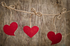 Three Red fabric hearts hanging on the clothesline stock photo