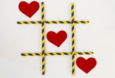 Three red felt hearts are lined up in a tic-tac-toe game, in a grid on a white background. The grid consists of colored tubes from royalty free stock photos