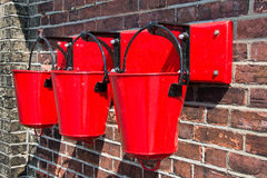 Three red fire buckets wall mounted Stock Photography