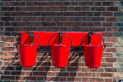 Three red fire buckets wall mounted Stock Photos