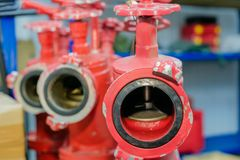 Three red fire hydrants with valves are in the warehouse royalty free stock photography