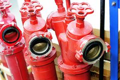 Three red fire hydrants with valves are in the warehouse royalty free stock image