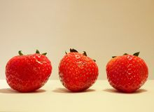 Three red fresh strawberries on white background Stock Images