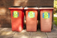 Three red garbage, trash bin eith writing stock image