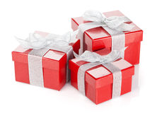 Three red gift boxes with silver ribbon and bow. Isolated on white background Stock Photos