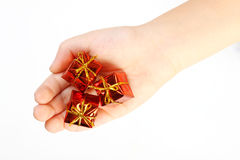 Three red gifts on a children's hand on white background. Gifts on kids palm. Royalty Free Stock Images