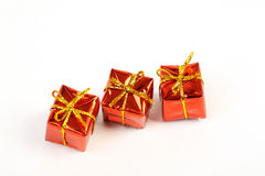 Three red glossy gift boxes with gold bow in the line on white background. Horizontal royalty free stock images