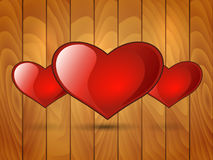 Three red glossy heart on a wooden background Royalty Free Stock Images
