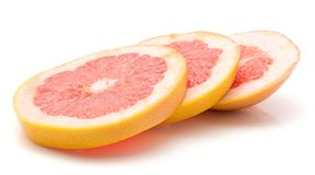Red grapefruit isolated. Three red grapefruit ring slices isolated on white background Royalty Free Stock Photo