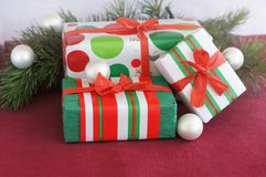 Three red-green-white Christmas gifts with white ornaments Stock Photos