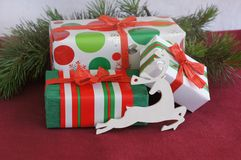 Three red-green-white Christmas gifts with white toy deer Stock Photo