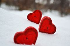 Three red hearts - candles on white snow, a gift for loved ones. stock photos