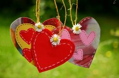 Three Red Hearts Hanging With White Flowers Royalty Free Stock Images