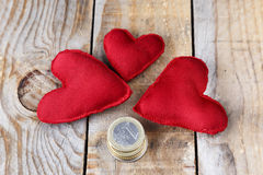Three red hearts made by hand. Next to some coins on an old wooden table Royalty Free Stock Photography