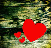 Three red hearts made of paper on the old dark wooden grunge background Stock Image