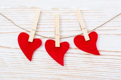 Three red hearts are piled by clothespins on a rope royalty free stock images
