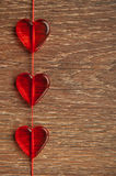Three red hearts on the wooden board Royalty Free Stock Photography