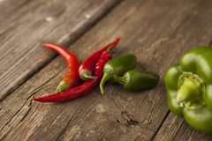 Three red hot chili peppers with green peppers Stock Photos