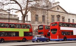 Three red London buses and a car on the street Stock Photography
