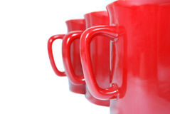 Three red mugs on white. Close up of three red mugs isolated on white background Royalty Free Stock Image