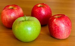 Three red and one green apple on table Stock Image