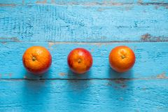 Three red oranges lie on a blue wood stock photos
